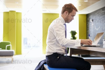 Businessman using laptop in an office meeting area, close up