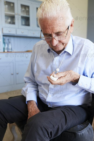 Senior Man At Home Using Distress Alarm Call Button