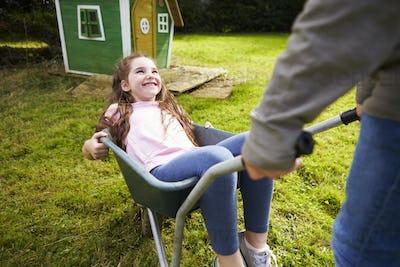 Brother Pushing Sister In Garden Wheelbarrow