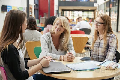 Teacher Talks To Students In Communal Area Of College Campus