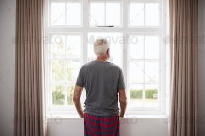 Rear View Of Senior Man In Pajamas Looking Out Of Bedroom Window