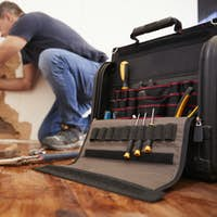 Middle aged man repairing burst pipe,plumbing, focus on foreground