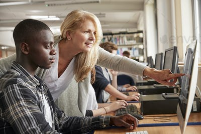 Teacher With Male Student Working On Computer In College Library