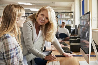 Teacher With Female Student Working On Computer In College Library