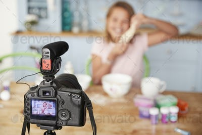 Young girl video blogging in kitchen seen through camera