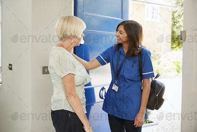 Nurse on home visit greets senior woman at her front door