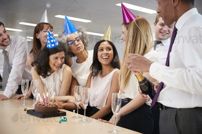 Colleagues celebrating a birthday in office open champagne