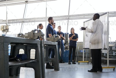 Engineering apprentices stand at a training presentation, low angle