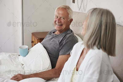 Retired Couple Wearing Pajamas Sitting In Bed Drinking Tea