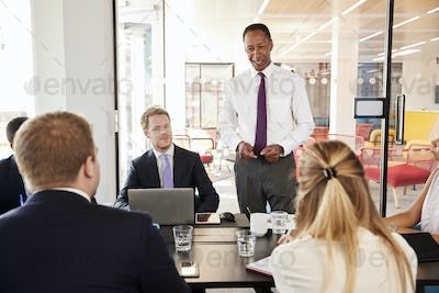 Black male manager addressing colleagues at a meeting smiles