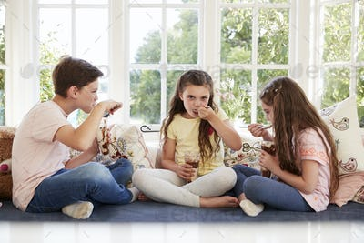 Children Sitting On Window Seat Eating Ice Cream Sundaes
