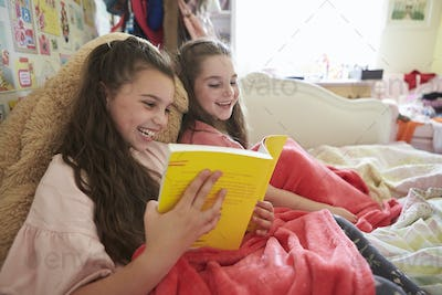Two Sisters Reading Book Sitting On Bed Together