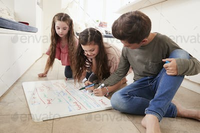Children Making List Of Chores On Whiteboard At Home