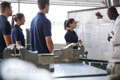 Engineer instructing four apprentices at white board