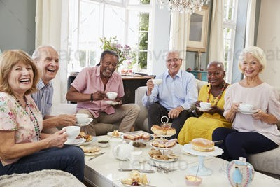 Portrait Of Senior Friends Enjoying Afternoon Tea At Home
