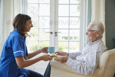Nurse serving a cup of tea to a senior man at home, close up
