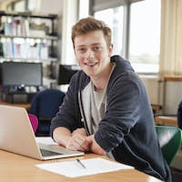 Portrait Of Male Student Working At Laptop In College Library