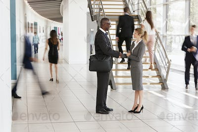Businessman and woman shaking hands in a modern building