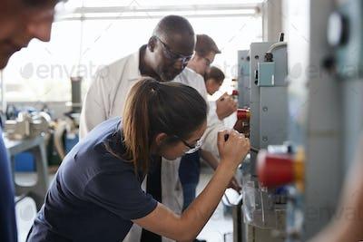 Engineer training female apprentice using a drill press