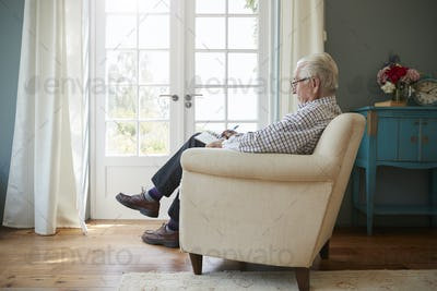 Senior man sitting in an armchair doing  crossword, side view