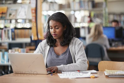 Mature Female Student Working On Laptop In College Library