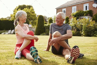 Healthy Senior Couple Exercising In Garden Together