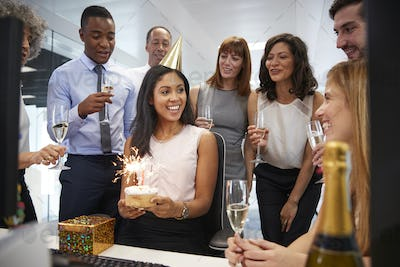 Colleagues gathered at woman's desk to celebrate a birthday