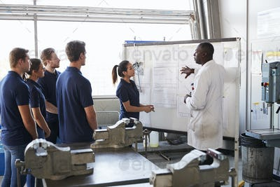 Engineer and female apprentice presenting at whiteboard