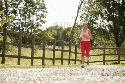 Healthy Senior Woman Enjoying Run Through Countryside