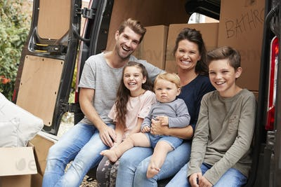 Family Sitting In Back Of Removal Truck On Moving Day