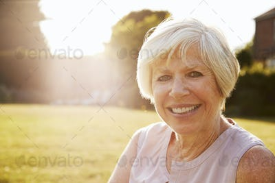Senior woman in the garden, smiling to camera, close up