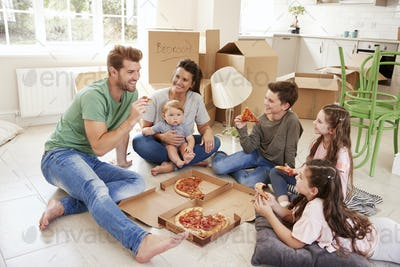 Family Celebrating Moving Into New Home With Pizza