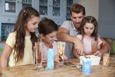 Father Making Ice Cream Sundaes With Children At Home