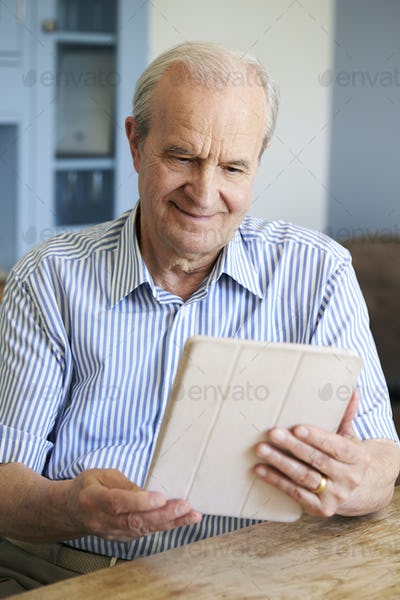 Senior Man Sitting At Home Using Digital Tablet At Table