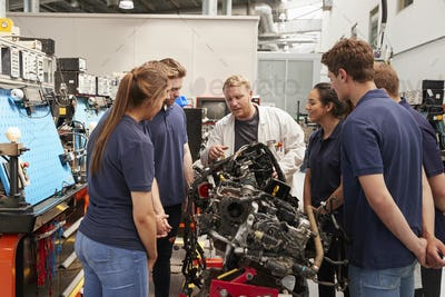 Car mechanic showing engines to apprentices