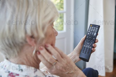 Senior woman using TV remote control, over shoulder view