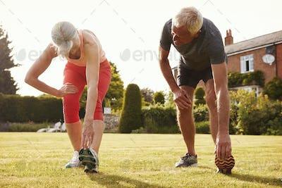 Healthy Senior Couple Exercising In Garden Together
