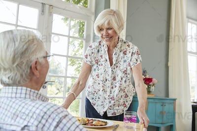 Senior woman serving dinner to senior man sitting at home
