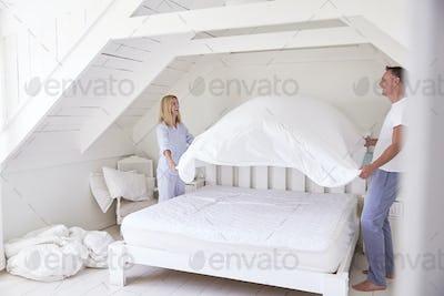 Couple Wearing Pajamas Making Bed In Morning