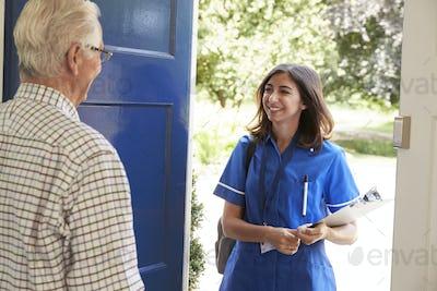 Senior man greeting female nurse making home visit