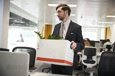 Fired male employee holding box of belongings in an office