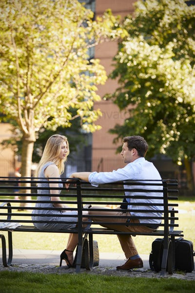 Businessman Talking To Female Colleague On Break In Park