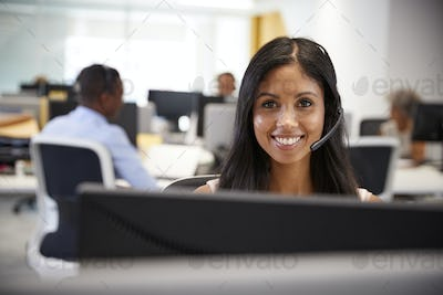 Young woman working at computer with headset in busy office