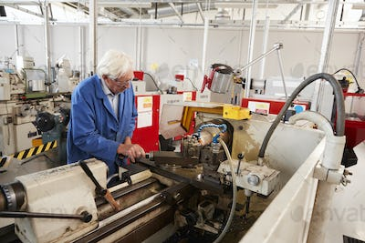 Senior engineer operating industrial machinery in a factory