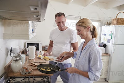 Mature Couple Chat In Kitchen As Woman Prepares Breakfast
