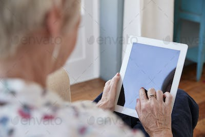 Senior woman using tablet computer, over shoulder view