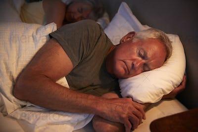 Peaceful Senior Man Asleep In Bed At Night
