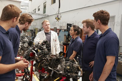 Apprentices studying car engines with a mechanic, close up