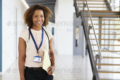 Smiling young female doctor with stethoscope and notes