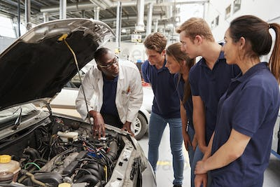 Mechanic instructing trainees around the engine of a car